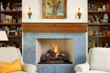 23 a refined fireplace clad with blue and white patterned tiles and with a rich stained wooden mantel