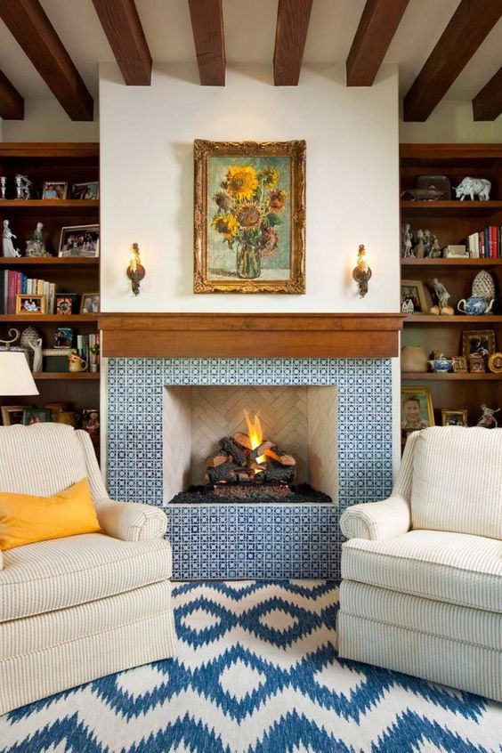 a refined fireplace clad with blue and white patterned tiles and with a rich stained wooden mantel