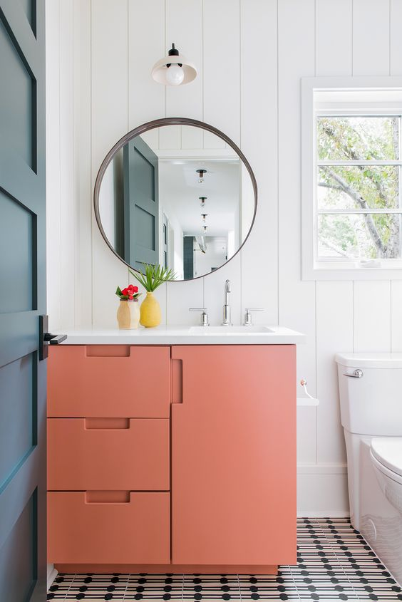 a tiny powder room done in a monochromatic color scheme and spruced up with a matte orange vanity with a white sink