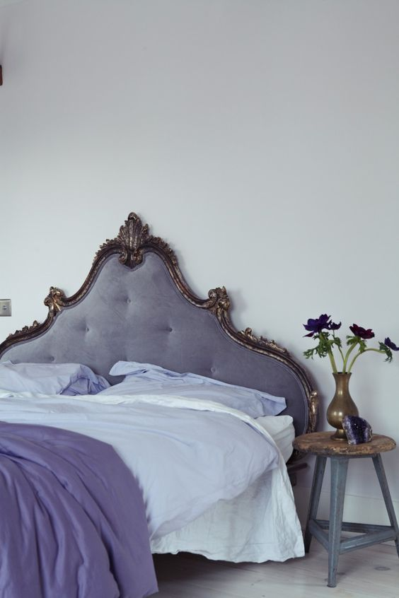 a very refined neutral bedroom accented with a lilac bed with a decorated headboard, with lilac and purple bedding and a chic brass vase