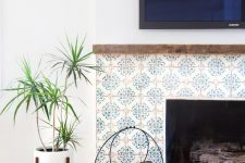 24 a stylish built-in fireplace clad with blue patterned tiles around it and with a delicate metal firewood stand next to it