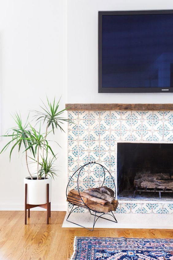 a stylish built-in fireplace clad with blue patterned tiles around it and with a delicate metal firewood stand next to it