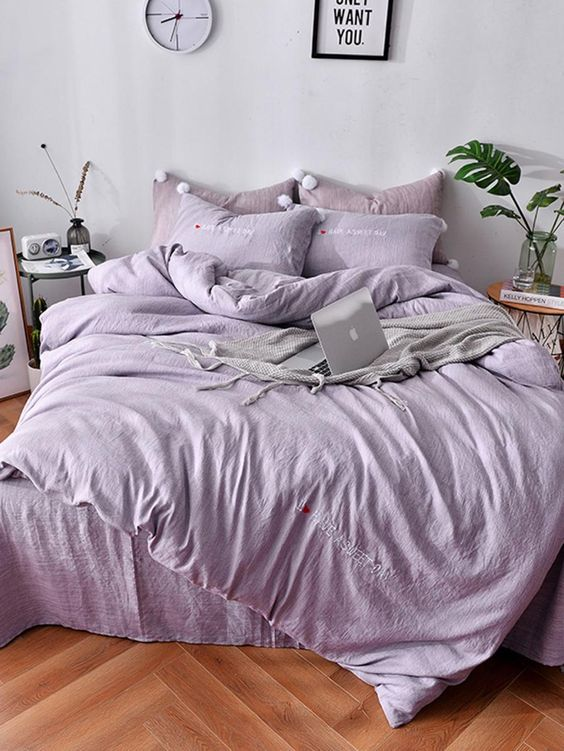a welcoming and relaxing monochromatic room with light lilac walls, lilac and dusty pink bedding, a lilac clock and various accessories