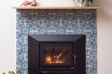 25 a stylish fireplace clad with blue patterned tiles around and blue glossy ones on the floor plus a simple wooden mantel is very vibrant