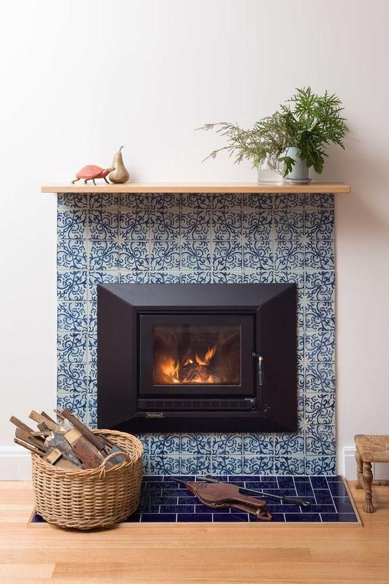 a stylish fireplace clad with blue patterned tiles around and blue glossy ones on the floor plus a simple wooden mantel is very vibrant