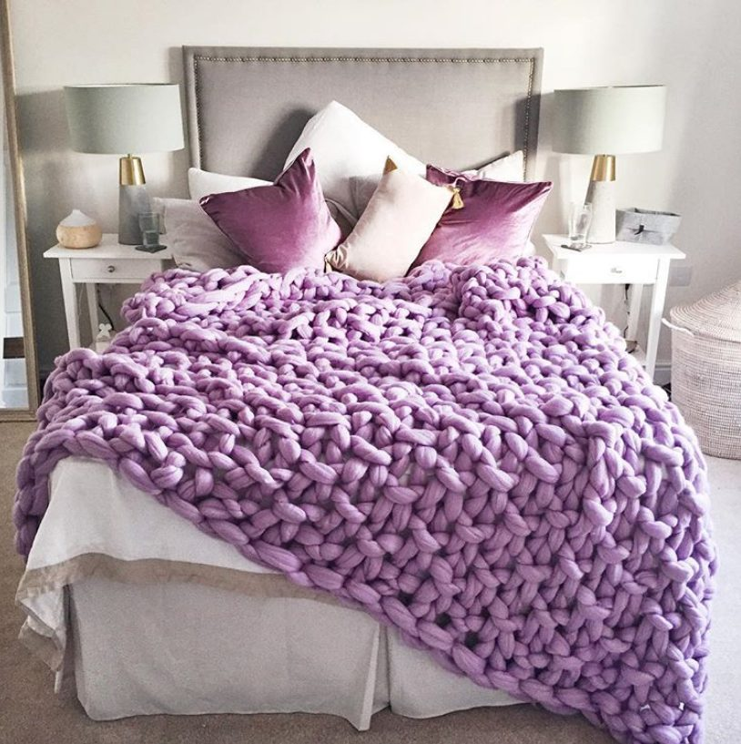 a white and grey bedroom with elegant and simple furniture and lamps and gorgeous purple pillows and a chunky knit blanket