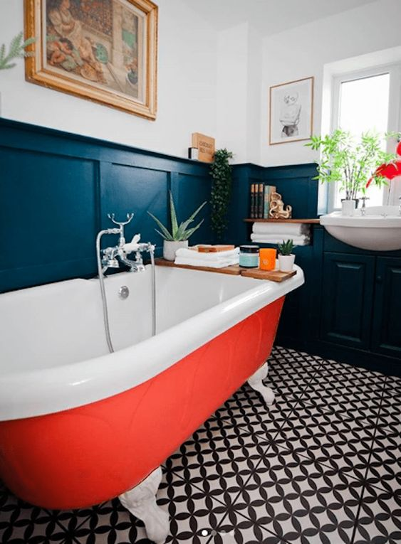 an elegant vintage-inspired bathroom with mosaic tiles on the floor, black paneling and an orange bathtub plus potted greenery