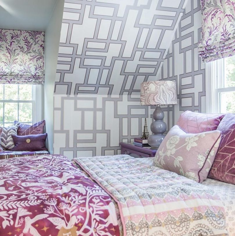 a white, grey and lilac bedroom with prined wallpaper, floral curtains, pink and lilac textiles is romantic and pretty