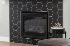 26 an ultra-modern built-in fireplace clad with black matte hexagon tiles and with a stained wooden mantel