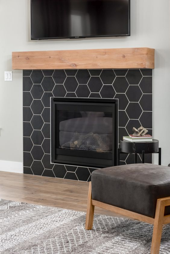 an ultra-modern built-in fireplace clad with black matte hexagon tiles and with a stained wooden mantel