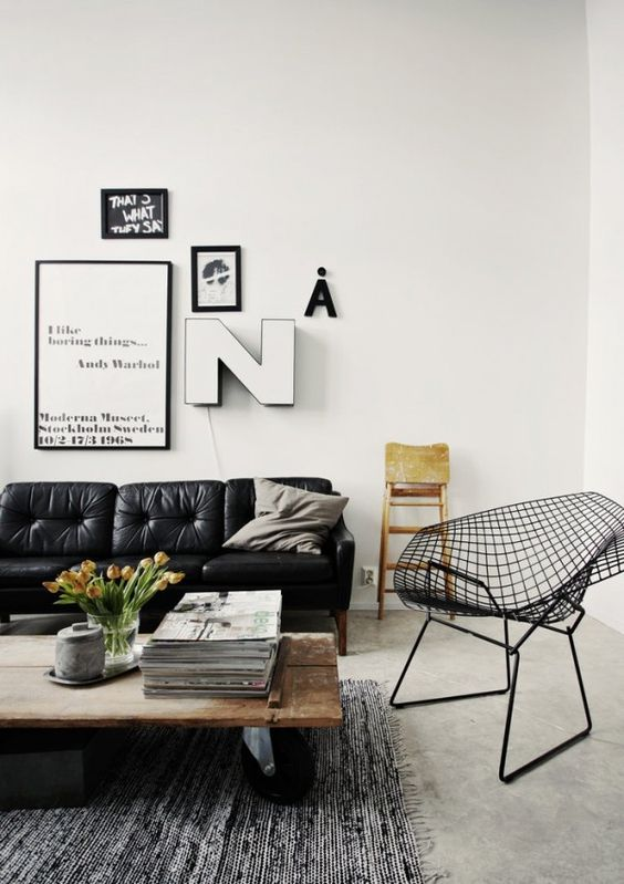 a Scandinavian living room with a black leather sofa, a wooden table on casters and a metal wire chair