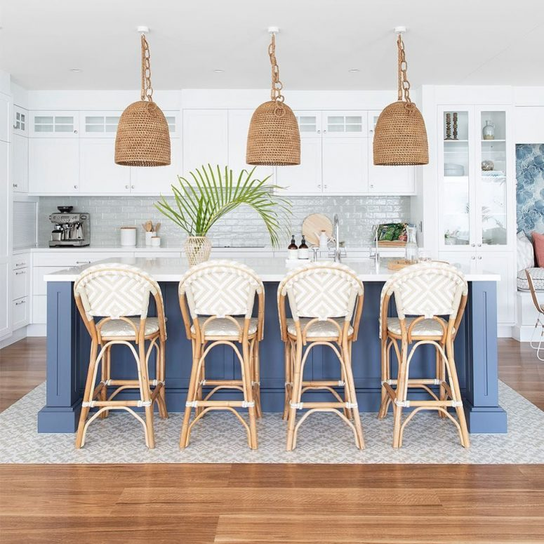 a beach kitchen with white cabinetry, a navy kitchen island, rattan chairs, woven lamps and greenery