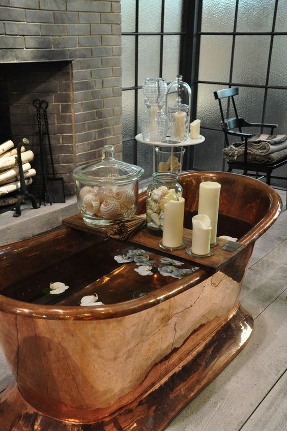 a beautiful bathroom with a non-working fireplace, elegant furniture, a copper bathtub and candles all around