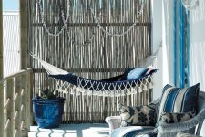 a beautiful beach porch with a navy hammock with tassels, white wicker chairs with blue upholstery and seashell garlands