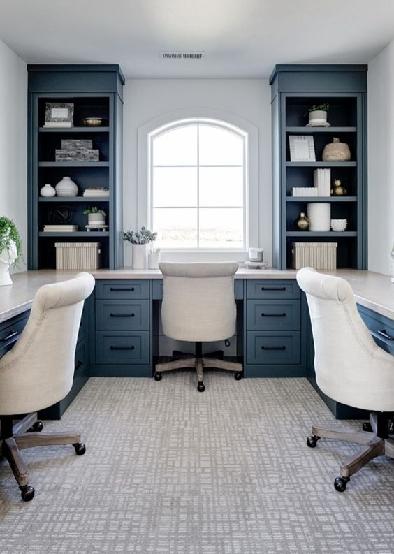 a beautiful blue and white home office with a long shared desk that goes along all the walls and stylish storage units by the window