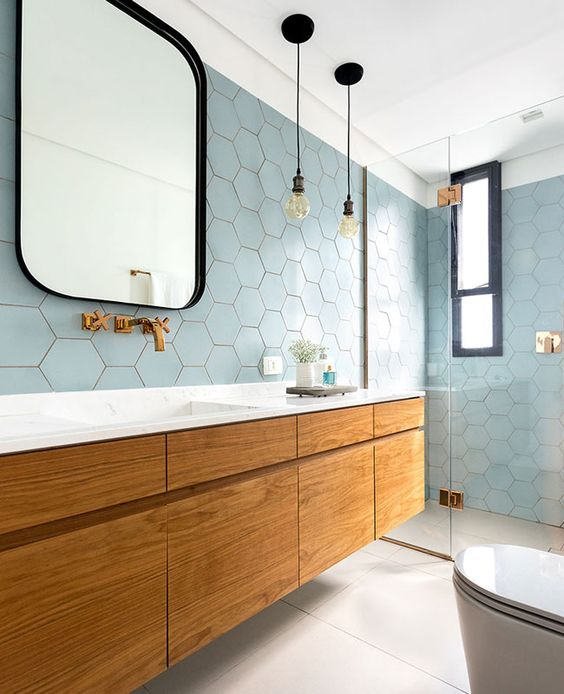 a beautiful coastal bathroom clad with light blue hex tiles, a large floating vanity, touches of black and brass
