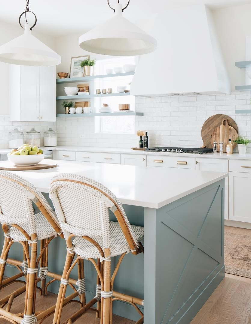 a beautiful coastal kitchen with white cabinets, light blue shelves and a matching kitchen island, rattan chairs and touches of gold