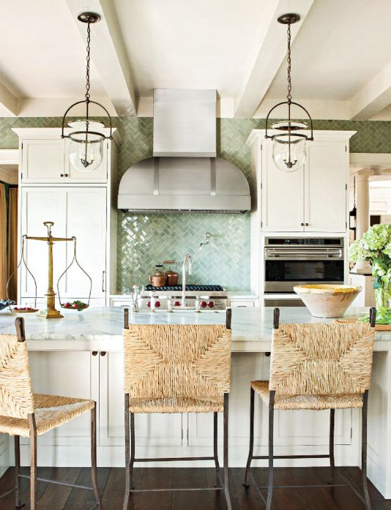 a beautiful coastal kitchen with white vintage cabinets, a large kitchen island with wicker chairs, glass pendant lamps and a green tile backsplash
