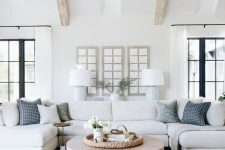 a beautiful coastal living room in white, with a U shaped sofa, grey chairs, printed pillows and jute and wood touches