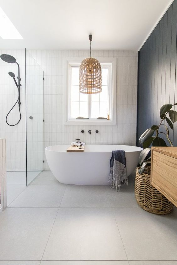 a beautiful contemporary coastal bathroom with a navy wooden wall, white skinny tiles, a woven lamp and a plant in a basket