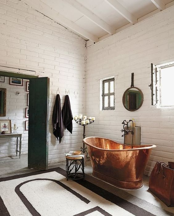 a beautiful vintage bathroom clad with white bricks, a copper bathtub that takes a center stage, a candelabra, a round mirror and a graphic rug