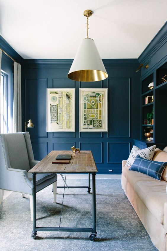 a blue home office with paneling on the walls and a stylish storage unit, neutral furniture, a white and gold lamp and a neutral chair