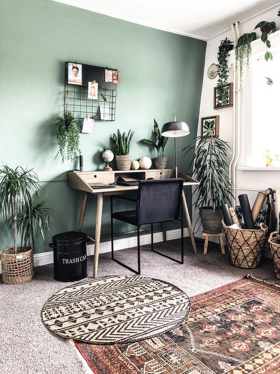 a boho chic home office with a green accent wall, stylish mid-century modern furniture, potted greenery and boho rugs