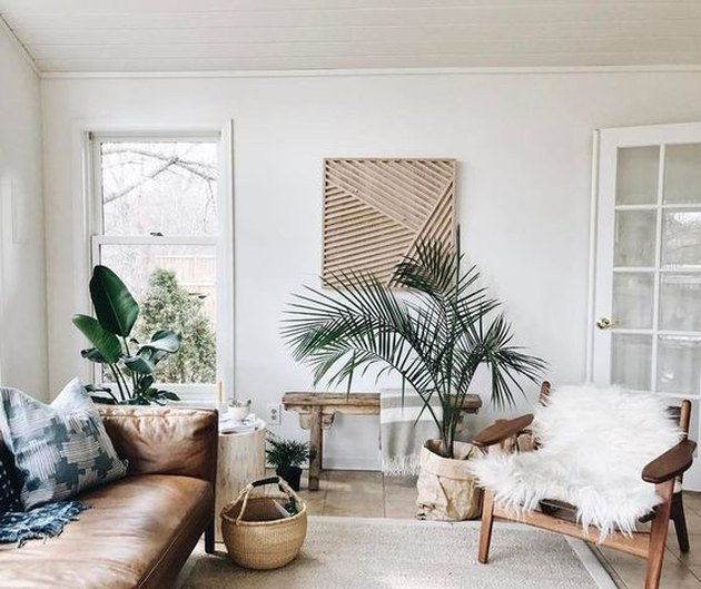 a boho tropical living room in neutrals, with a leather sofa, a fur chair, a wooden bench, baskets and potted plants