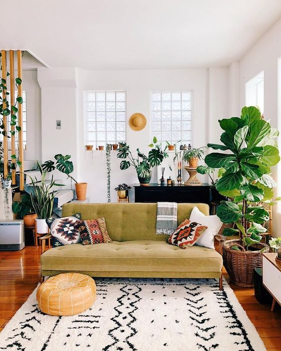 a boho tropical space with a green sofa, boho pillows, lots of potted plants and a printed rug