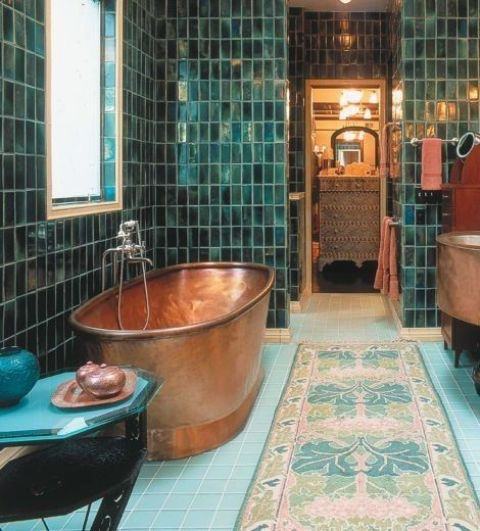 a bold Moroccan-inspired bathroom clad with green and blue tiles, a copper bathtub and refined furniture