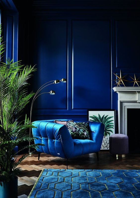 a bold art deco living room with bright paneled walls, a bright chair and a rug, jewel tones and touches of gold