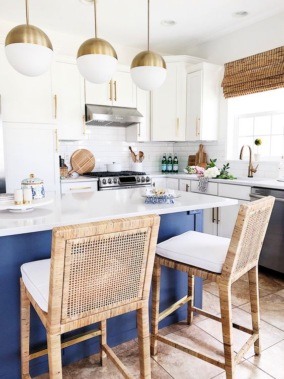 a bold coastal kitchen with white cabinets, a navy kitchen island with a white countertop, rattan chairs, woven shades and open shelves