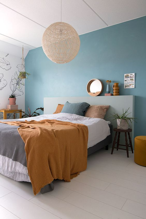 a bold contemporary bedorom with a blue accent wall, a grey headboard, a woven lamp and catchy bedding