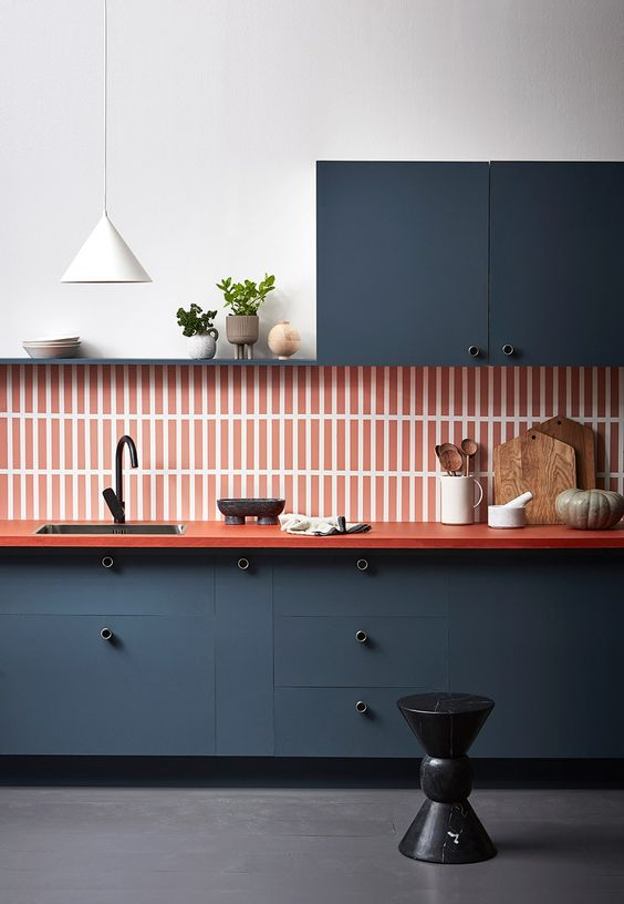 a bold graphite grey kitchen with a burnt orange tile backsplash and countertops and white accessories