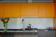 a bold minimalist kitchen with orange sleek upper cabinets and greyish lower ones, a white tile backsplash to refresh
