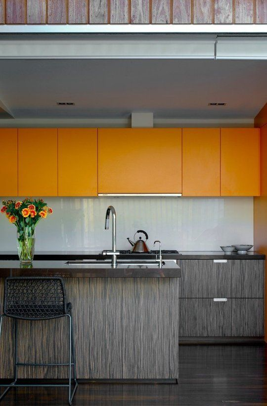 a bold minimalist kitchen with orange sleek upper cabinets and greyish lower ones, a white tile backsplash to refresh
