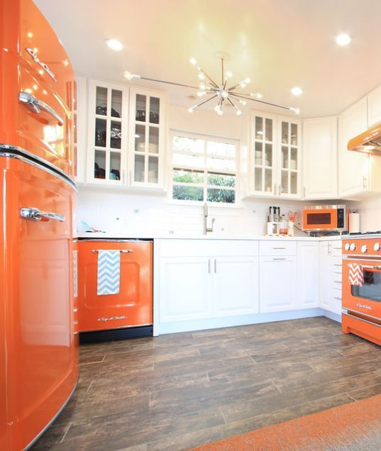 a bold modern kitchen with white and orange cabinets, a sunburst chandelier and an orange fridge is cool