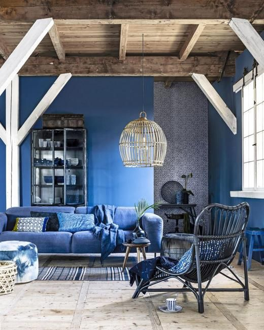 a bold monochromatic living room with bold blue walls, a matching sofa and chair plus matching textiles