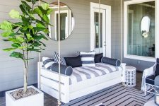 a bold nautical porch with a suspended upholstered daybed, white metal furniture and navy textiles, a potted tree