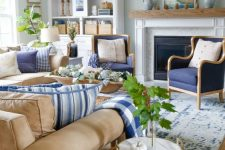 a bold navy and tan living room with aqua walls, greenery, a woven ottoman, a fireplace and pampas grass