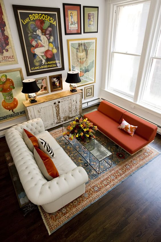 a bold refined living room with a white leather and orange fabric sofa and a statement gallery wall that creates a mood