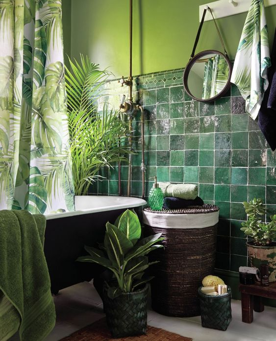 a bold tropical bathroom with green walls, green glazed tiles, a black tub, potted greenery and plants, green towels