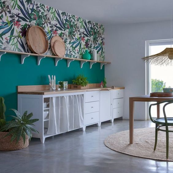 a bold tropical kitchen with an emerald and bright tropical wallpaper wall, white cabinets with a curtain, a wicker pendant lamp