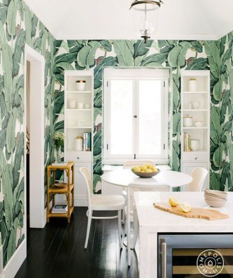 a bold tropical kitchen with banana leaf wallpaper, white furniture and a dining set with rattan chairs