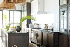 a bold tropical kitchen with white walls, dark stained cabinets, woven pendant lamps and baskets plus tropical leaves