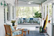 a bright and fun coastal porch with a hanging daybed and a chair with an ottoman, blue pritned textiles and a yellow surf board