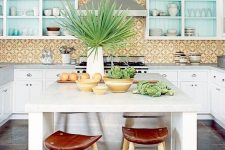 a bright and fun kitchen with a yellow tile backsplash, blue cabinets and a kitchen island with wooden stools