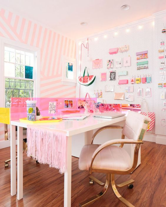 a bright and glam home office with a pink striped accent wall, a pegboard wall with lots of stuff, two desks and pink fringe