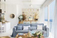 a bright and welcoming beach living room with a glazed wall, blue sofas, a wooden coffee table, a cool gallery wall and a beach sideboard