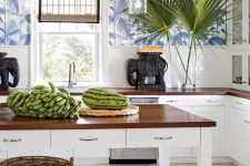 a bright and welcoming tropical kitchen with blue tropical leaf wallpaper, white subway tiles and cabinets plus baskets